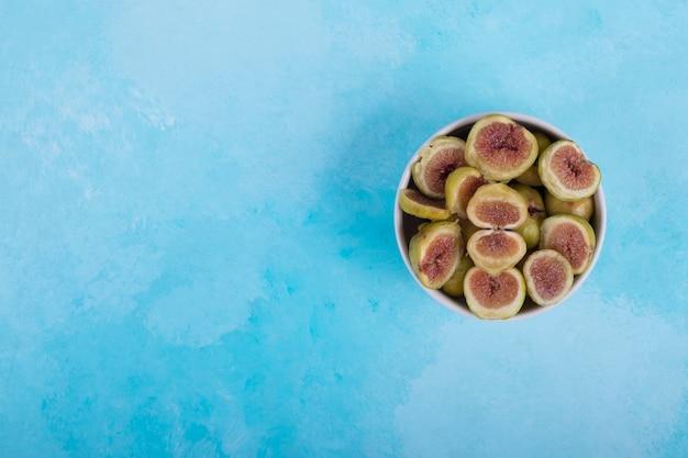Zielone figi z czerwonymi nasionami w białej ceramicznej misce, widok z góry