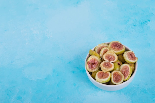 Zielone figi z czerwonymi nasionami w białej ceramicznej misce.