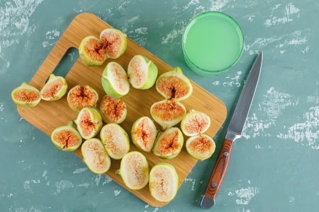 Zielone figi z napojem, nóż płasko ułożony na tynku i deska do krojenia