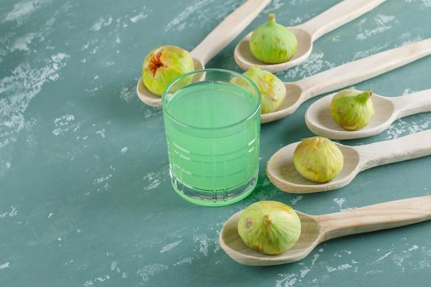 Zielone figi z napojem w drewnianych łyżkach na ścianie gipsowej, widok z góry.