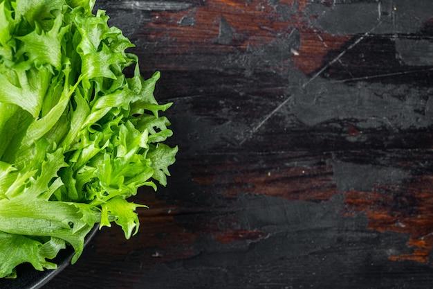 Zielone frillies liście sałaty lodowej, na starym ciemnym tle drewnianego stołu, widok z góry płasko leżał z miejscem na kopię dla tekstu