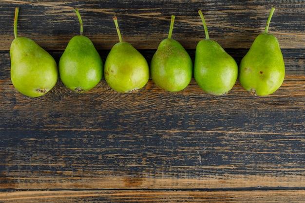 Zielone gruszki leżały płasko na drewnianym tle