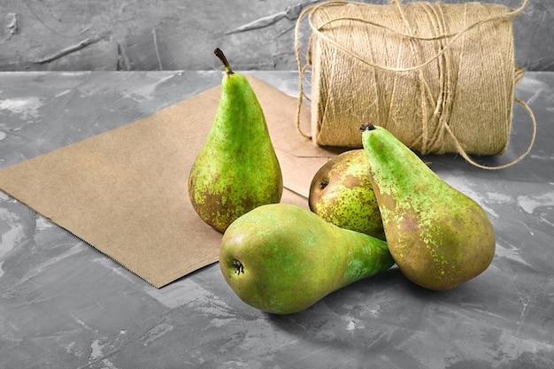 Zielone gruszki na szarym tle z papierową torbą do dostawy, dostawy żywności, opakowania środowiska.