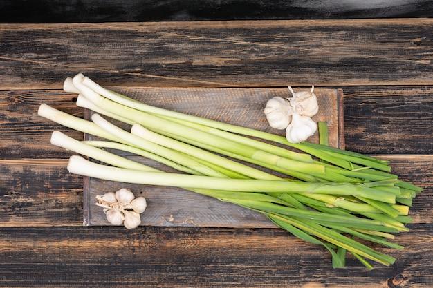 Zielone i białe szczypiorek na desce do krojenia