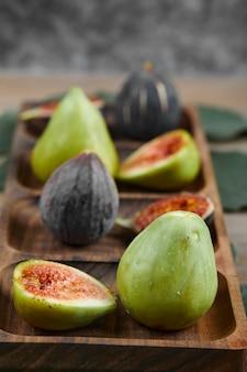 Zielone i czarne figi na drewnianym talerzu z liśćmi i obrusem, z bliska. wysokiej jakości zdjęcie