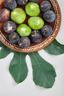 Zielone i czarne figi na talerzu ceramicznym i na białym tle. wysokiej jakości zdjęcie