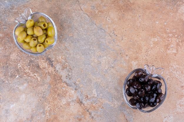 Zielone i czarne oliwki w szklanych kubkach