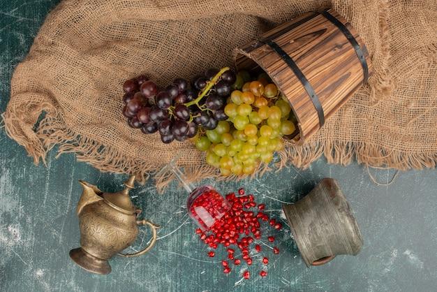 Zielone i czarne winogrona i pestki granatu na marmurowej powierzchni.