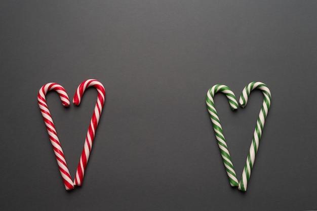 Zielone i czerwone cukierki w kształcie serca na szarym tle