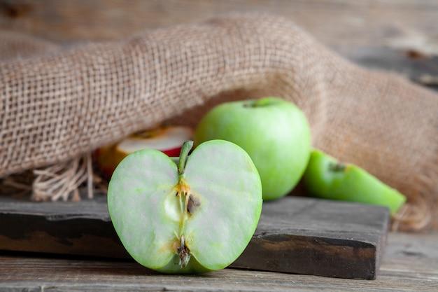 Zielone i czerwone jabłka pokroić na pół na tle drewna, tkaniny i ciemnego drewna. widok z boku.