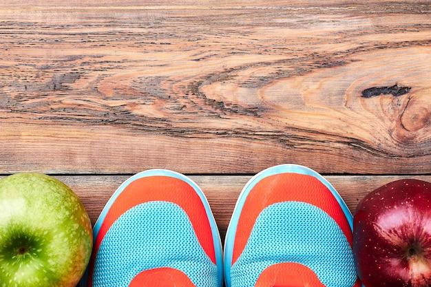 Zielone i czerwone jabłka. trampki na drewnianej powierzchni. sport czyni twoje życie zdrowym.