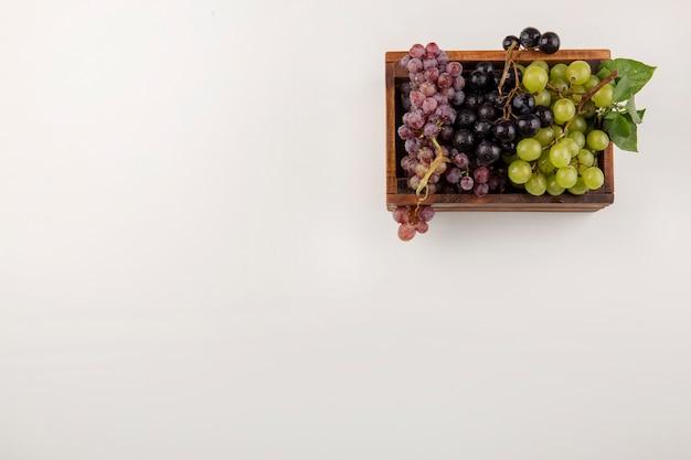 Zielone i czerwone kiście winogron w drewnianym pudełku w rogu