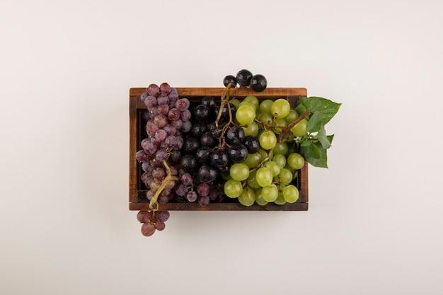 Zielone i czerwone kiście winogron w drewnianym pudełku w środku