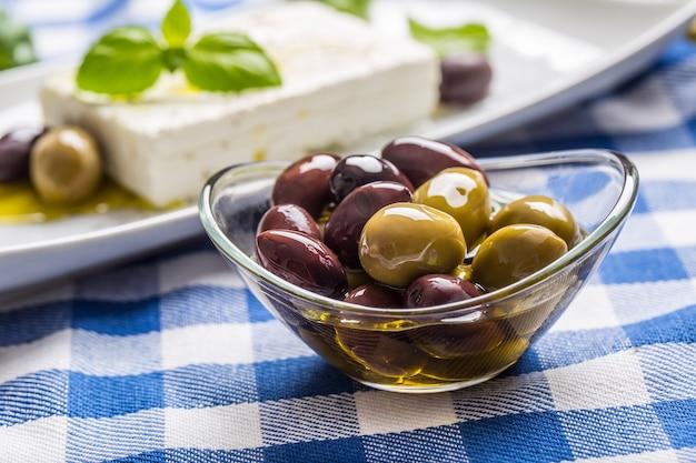 Zielone i czerwone oliwki w misce z oliwą z oliwek i greckim serem feta w tle.