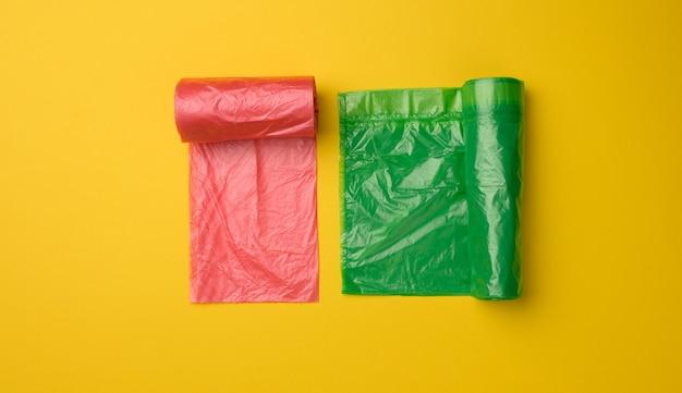 Zielone i czerwone plastikowe torby na kosz na śmieci na żółtym tle, widok z góry
