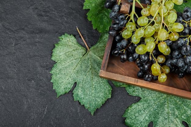 Zielone i czerwone winogrona w drewnianej tacy.