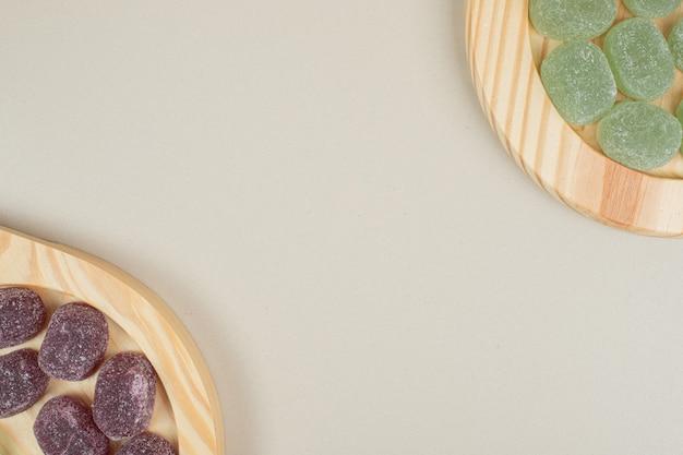 Zielone i fioletowe galaretki cukierki na drewnianych talerzach