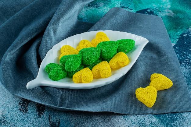 Zielone i żółte ciasteczka na talerzu na kawałkach tkaniny, na niebieskim tle.