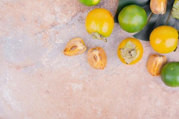 Zielone i żółte mandarynki na różowym stole.