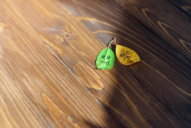 Zielone i żółte opadłe liście z symbolami szczęśliwych i smutnych twarzy