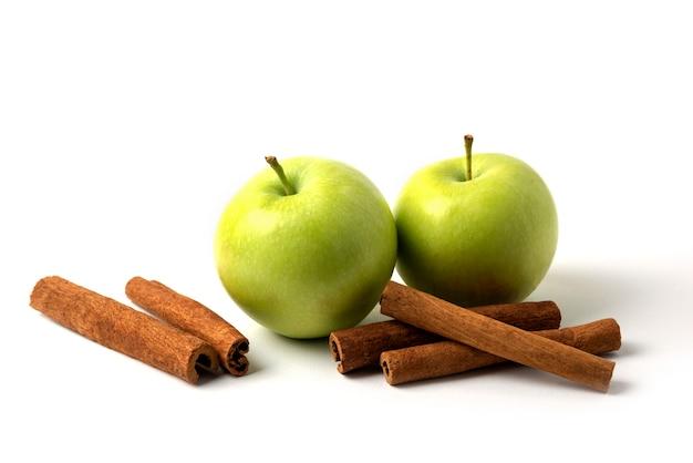 Zielone jabłka i cynamony na białym tle