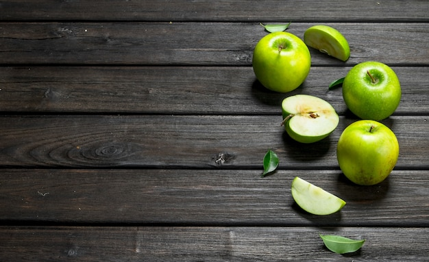 Zielone jabłka i plasterki jabłka. na ciemnej drewnianej powierzchni.