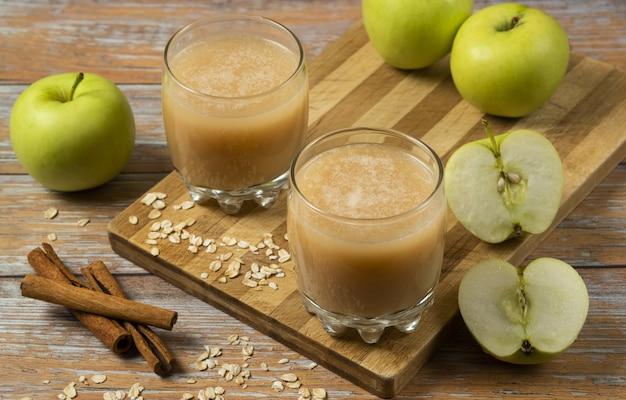 Zielone jabłka, laski cynamonu i dwie filiżanki świeżego soku na stole, widok z góry