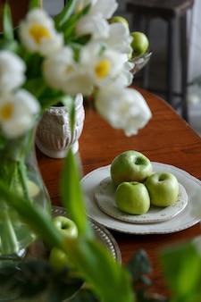 Zielone jabłka na białym porcelanowym talerzu na brązowym drewnianym stole