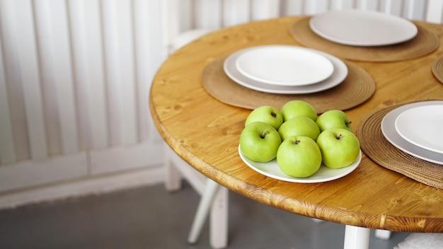 Zielone jabłka na białym talerzu na drewnianym stole. białe nowoczesne wnętrze w stylu skandynawskim