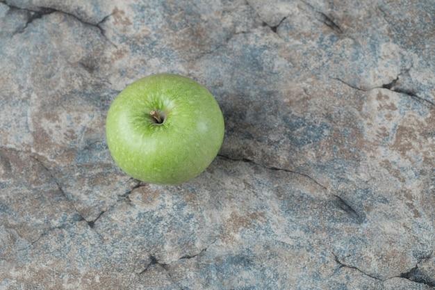 Zielone jabłka na białym tle na betonie.