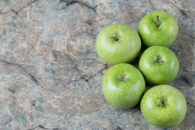 Zielone jabłka na białym tle na betonowej powierzchni