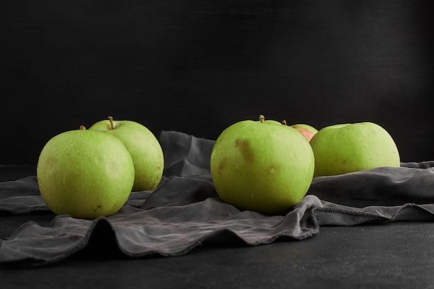 Zielone jabłka na białym tle na czarnym tle na szarym obrusie.