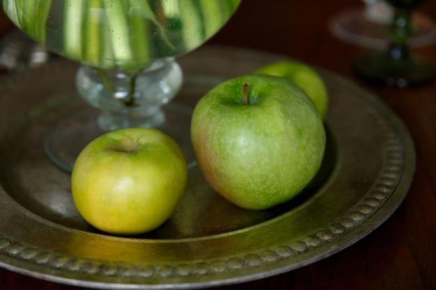 Zielone jabłka na metalowej tacy na stole