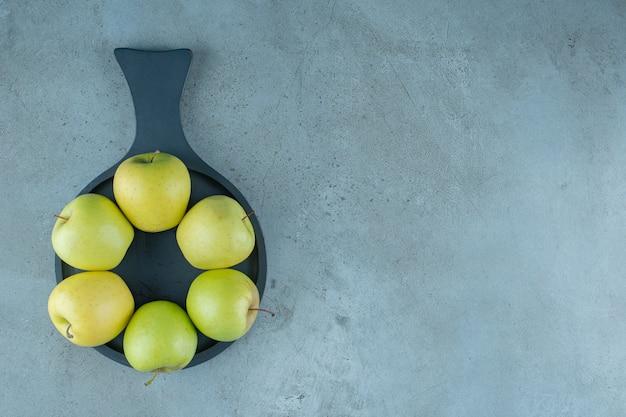 Zielone jabłka na patelni, na marmurowym tle. zdjęcie wysokiej jakości