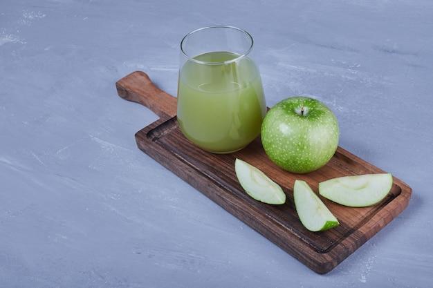 Zielone jabłka popijając szklanką soku.