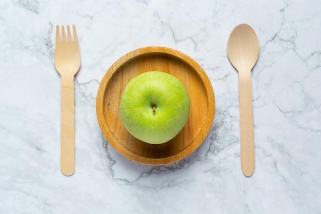 Zielone jabłka umieszczamy w drewnianej misce obok drewnianej łyżki i widelca
