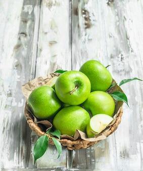 Zielone jabłka w koszu.