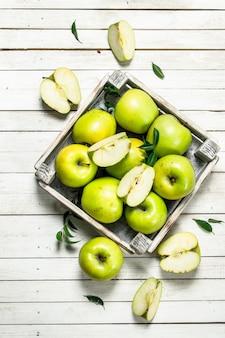 Zielone jabłka w małym pudełku.