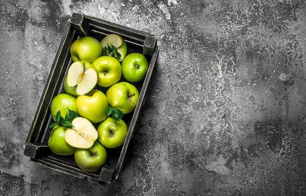Zielone jabłka w starym pudełku. na rustykalnym tle.