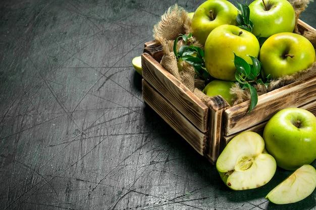 Zielone jabłka w starym pudełku.