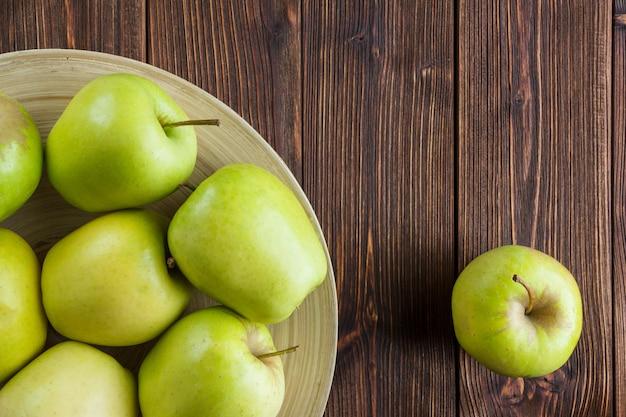 Zielone jabłka w talerzu i wokół widoku z góry na drewnianym tle miejsca na tekst