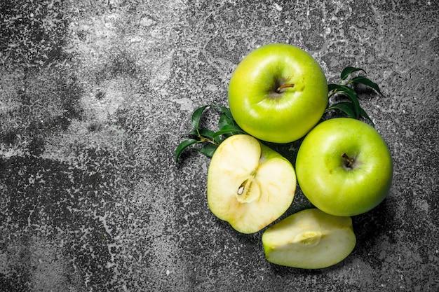 Zielone jabłka z liśćmi. na rustykalnym tle.