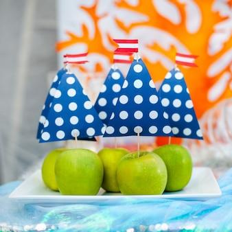 Zielone jabłka z niebieskim żaglem