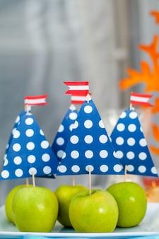 Zielone jabłka z żaglem z papieru. motyw czasu morskiego na batoniku imprezowym