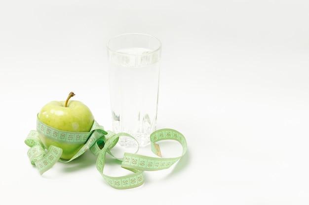 Zielone jabłko, centymetr i szklanka wody na białym tle