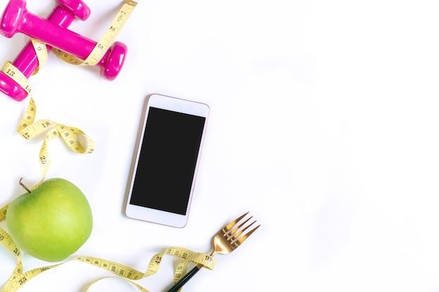 Zielone jabłko, hantle, taśma miernicza i telefon na tle białego stołu. dieta, schudnąć koncepcja