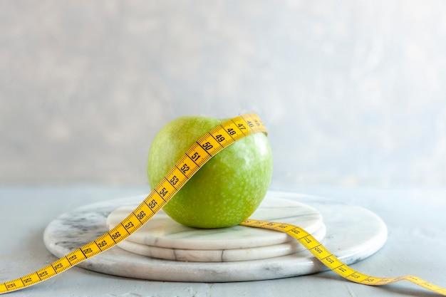 Zielone jabłko i centymetr. świeże owoce, koncepcja odchudzania, dieta, dieta ketogeniczna, przerywany post