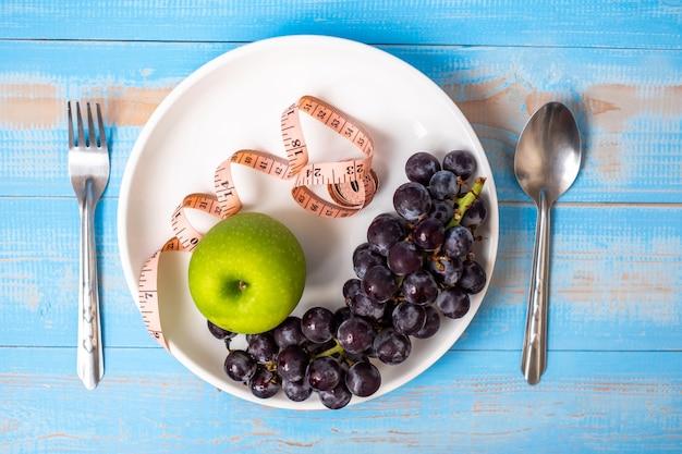 Zielone jabłko i czarne winogrona w białym naczyniu z różową taśmą mierniczą