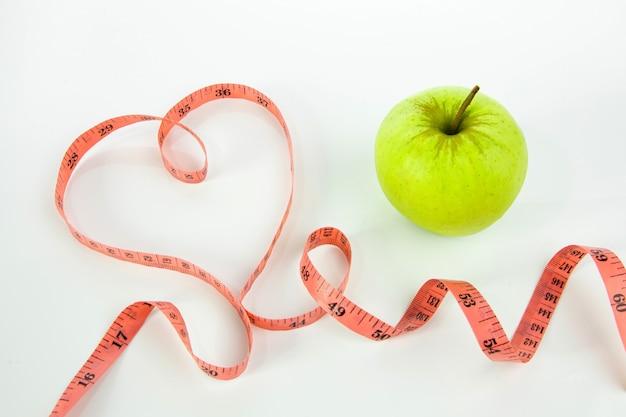 Zielone jabłko i miarka w kształcie serca na białym tle