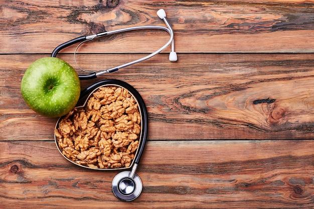 Zielone jabłko i orzechy włoskie. stetoskop na drewnianej brązowej powierzchni.